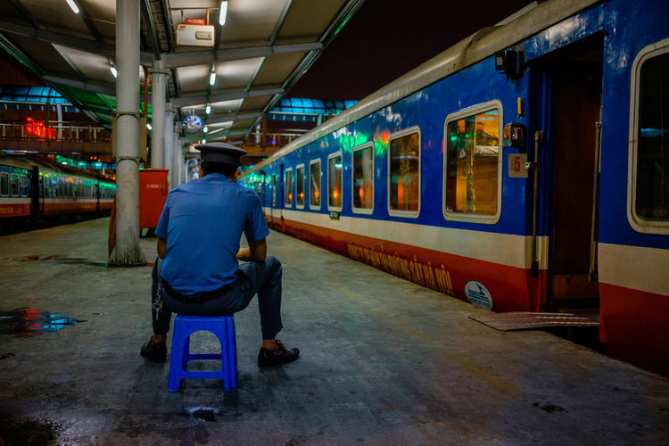 Rear view of man sitting on train at railroad station