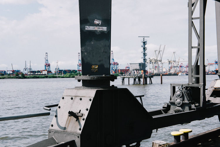 Cranes at dock in sea against sky