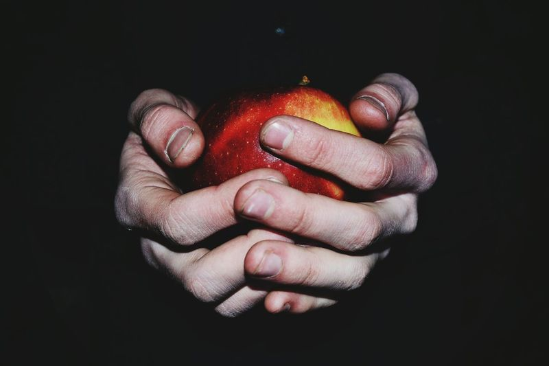 Close-up of hand holding strawberry over black background