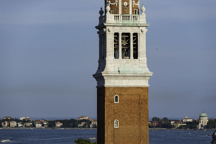 Clock tower by sea against sky in city