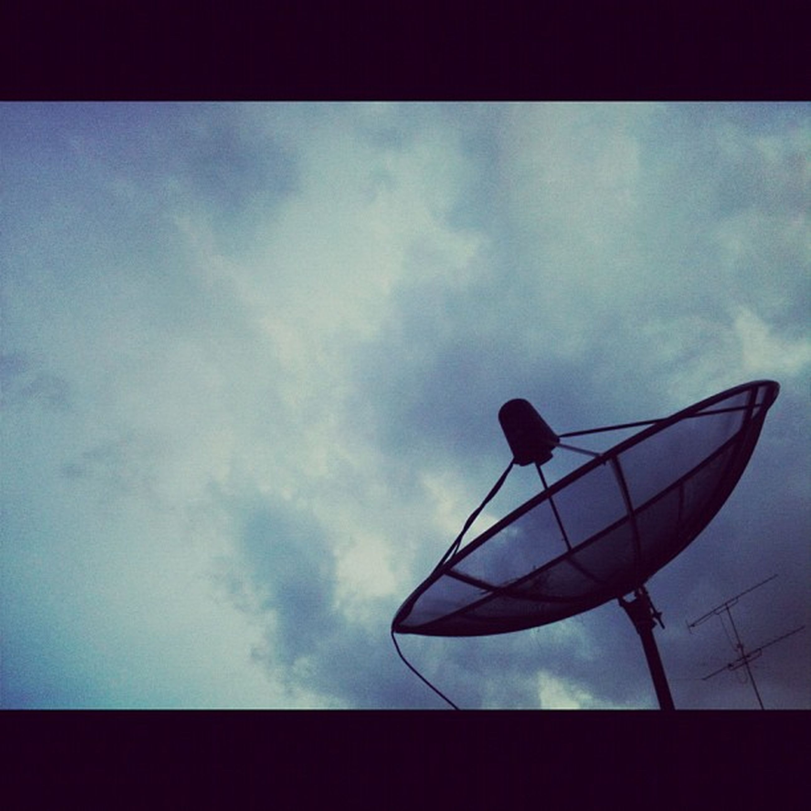 sky, low angle view, transfer print, cloud - sky, auto post production filter, cloud, cloudy, silhouette, no people, street light, day, outdoors, dusk, nature, lighting equipment, overcast, pole, tranquility, vignette, transportation