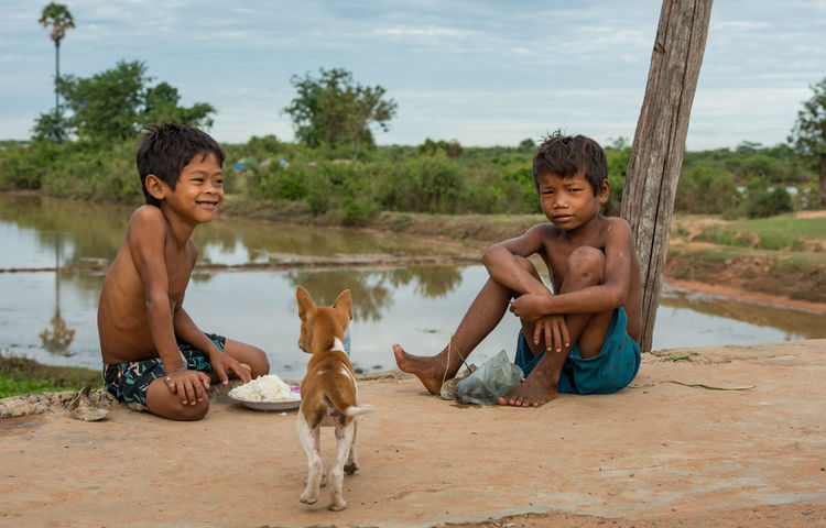 Breakfast with friends. Beauty In Nature Boys Breakfast Time Cambodia Care Child Dog Friendship Happiness Khmer Outdoors Pets Rice Rural Scene Sharing  Sitting Togetherness Travel Tropical Climate