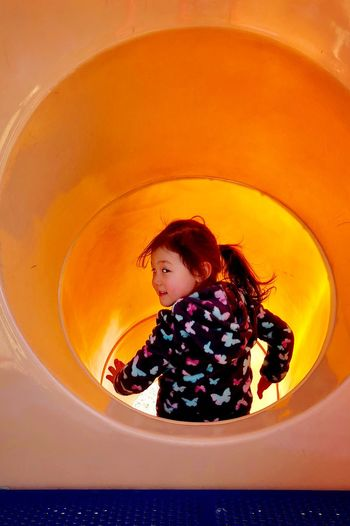 Portrait of girl playing in slide