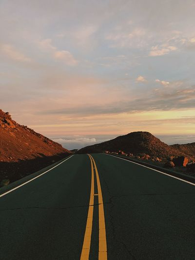 Diminishing perspective of empty road against cloudy sky during sunset