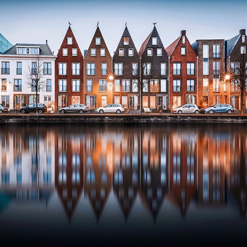 Reflection of residential buildings by river at dusk