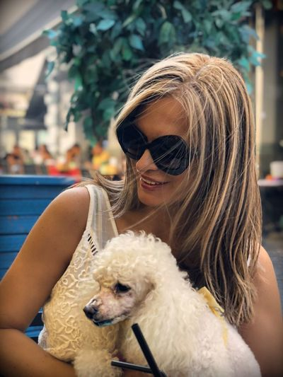 Smiling woman wearing sunglasses carrying dog in city