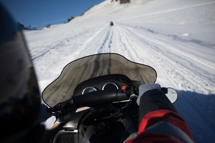 Person riding snowmobile on mountains