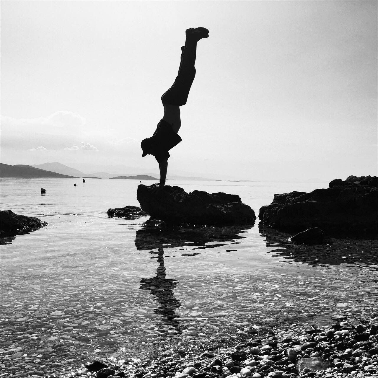 skill, full length, flexibility, balance, water, exercising, day, vitality, outdoors, concentration, upside down, sea, real people, lifestyles, one person, handstand, performance, legs apart, women, young women, nature, young adult, sky, people