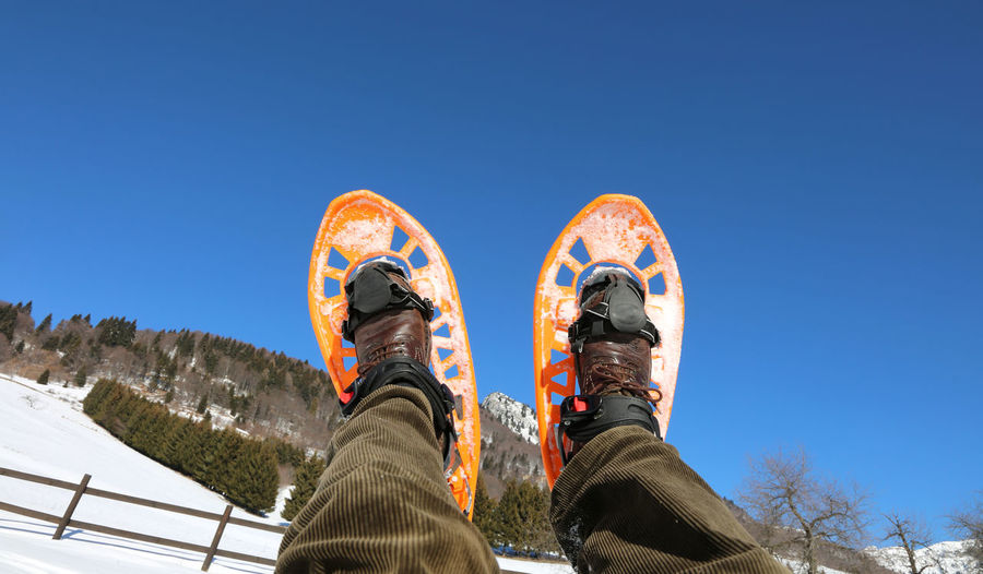 Woman Snowshoeing Against Clear Blue Sky