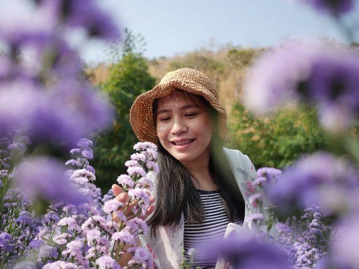 Portrait of smiling young woman against purple flowering plants