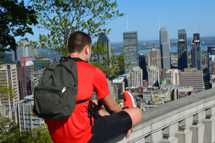 Man in sportswear looks at the skyline of Montréal, Canada. City Life Cityscape Man In Sportswear Man Looking At Skyline Montréal Real People Skyline Of Montreal Sportive Man In City Sportswear Urban Skyline Young Adult