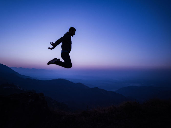 Silhouette man jumping on mountains against sky at dusk