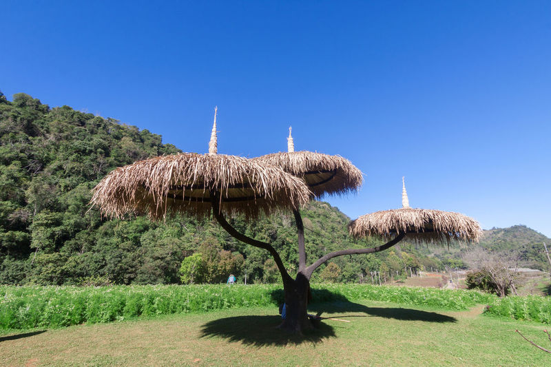 Traditional windmill on landscape against clear blue sky