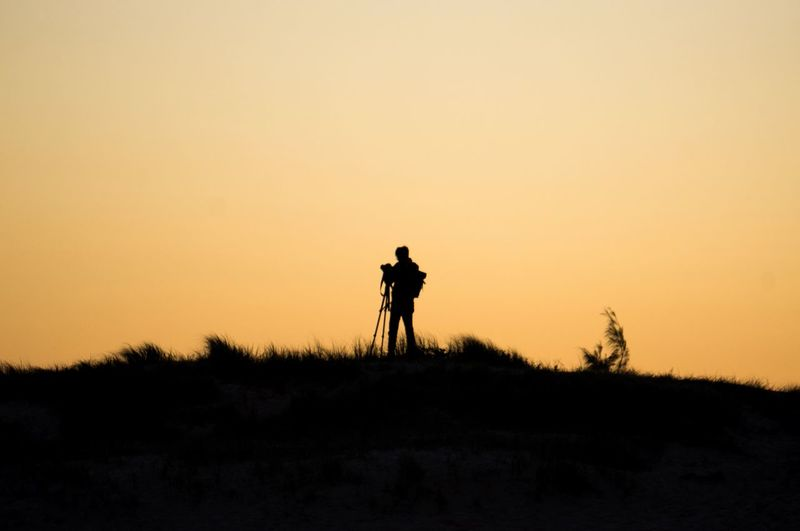 Silhouette person photographing on field against sky during sunset