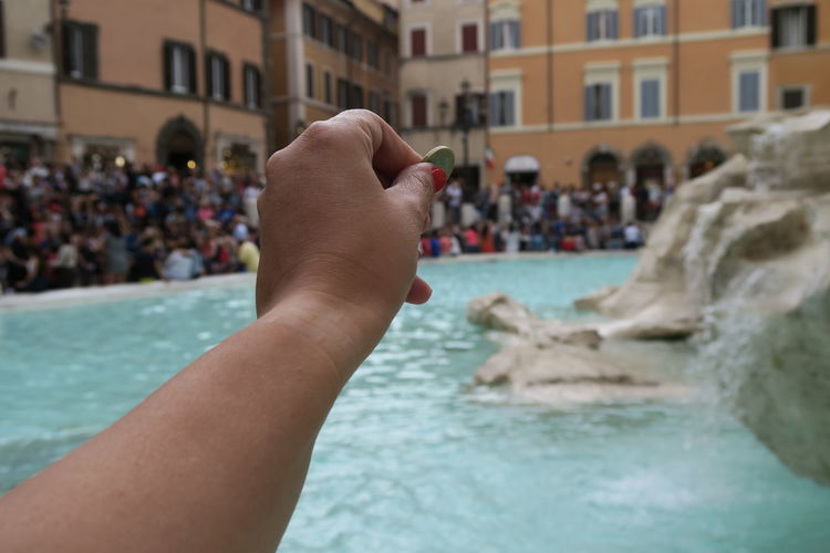 Rome, Italy – summer. Throw a coin at the renovated Fontana di Trevi. The Trevi fountain, after its renovation, gathers daily large crowds. Tradition says that tossing a coin here will make you return to Rome. Capital Cities  City Life Coin Famous Place Focus On Foreground Fontana Di Trevi Italia Italian Italy Landmark Outdoors Roma Roman Rome Rome Italy Selective Focus Tourism Tourist Tourist Attraction  Tourist Destination Travel Destinations Travel Photography Trevi Trevi Fountain TreviFountain Moving Around Rome