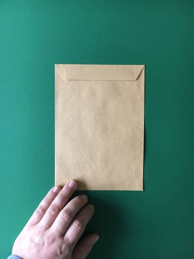 Cropped image of hand with envelop on green background