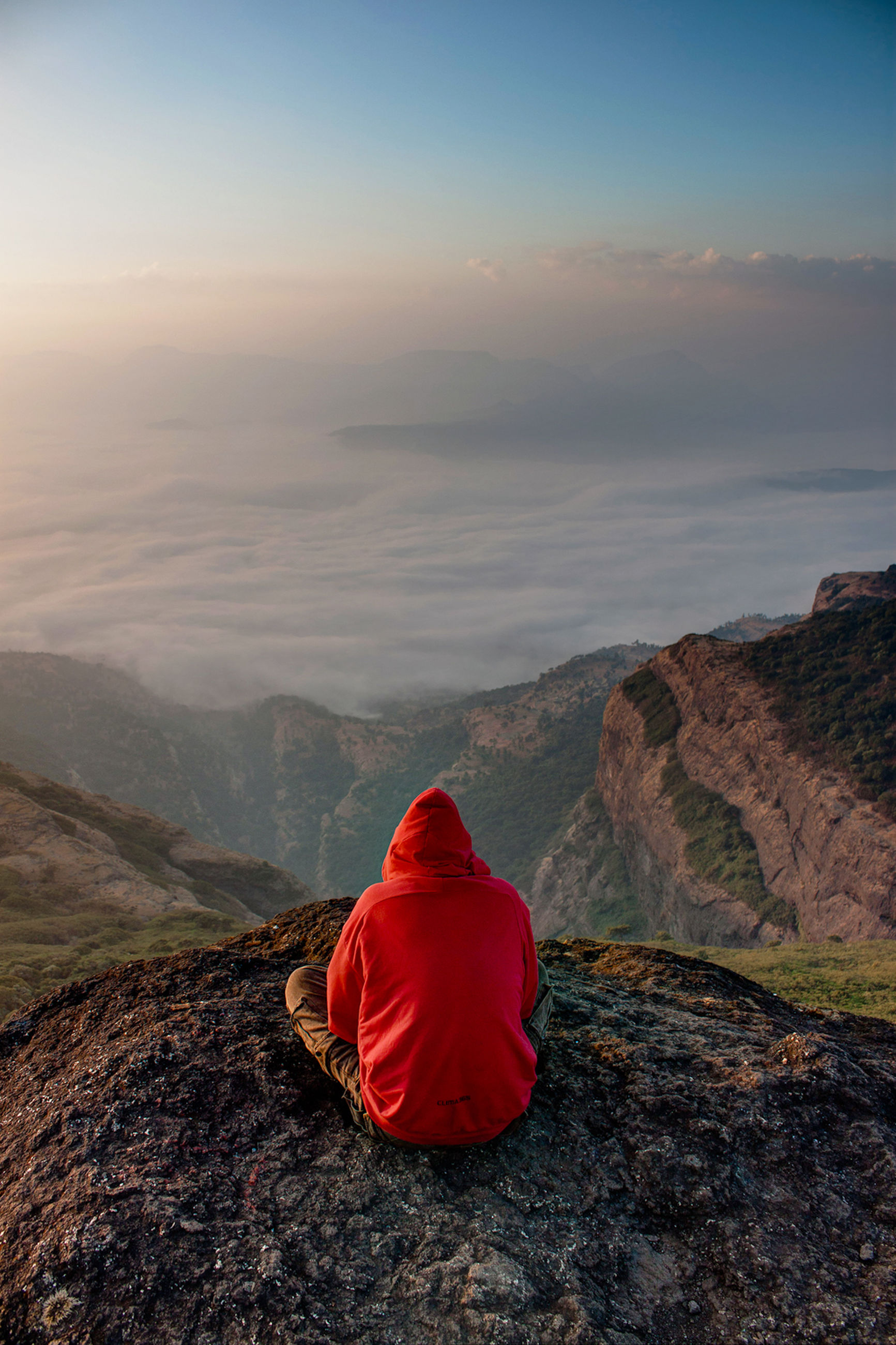 rear view, beauty in nature, sky, scenics - nature, tranquility, tranquil scene, mountain, one person, rock, non-urban scene, real people, rock - object, solid, cloud - sky, nature, red, idyllic, environment, sitting, remote, mountain range, outdoors, hood - clothing, looking at view