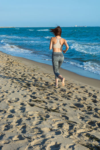 Full Length Of Woman Running On Sand At Beach