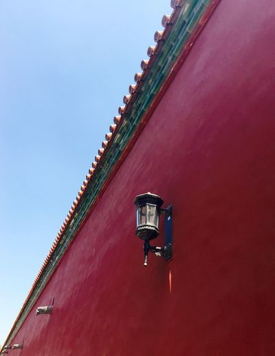 Low angle view of lamp on red wall against clear sky