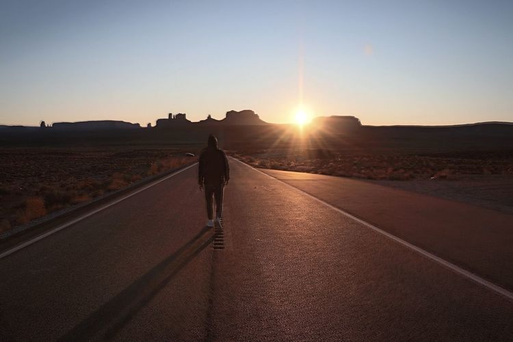 Rear view of man walking on road against sky during sunset