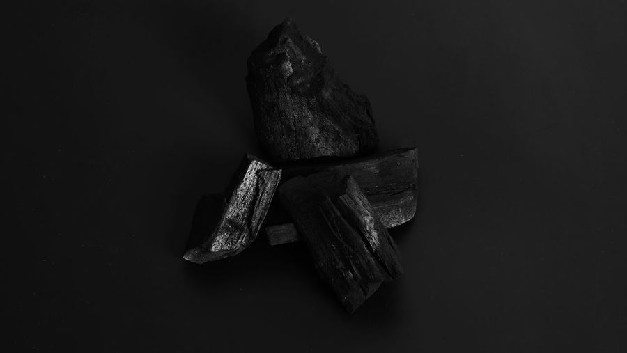 High angle view of meat on rock against black background