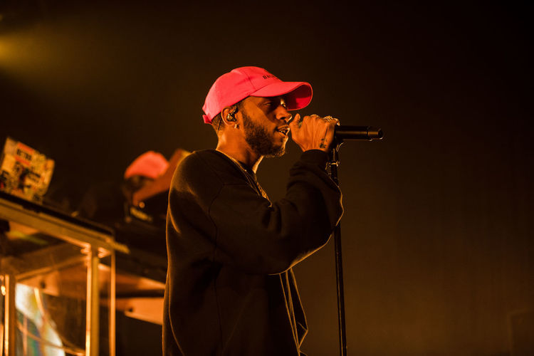 One Person Men Holding Hat Waist Up Standing Males  Real People Clothing Music 6lack Rap Rapper HipHop Hip Hop Concert Photography Concert Festival ATL Atlanta Rappers Microphone Portrait Look Away Dark