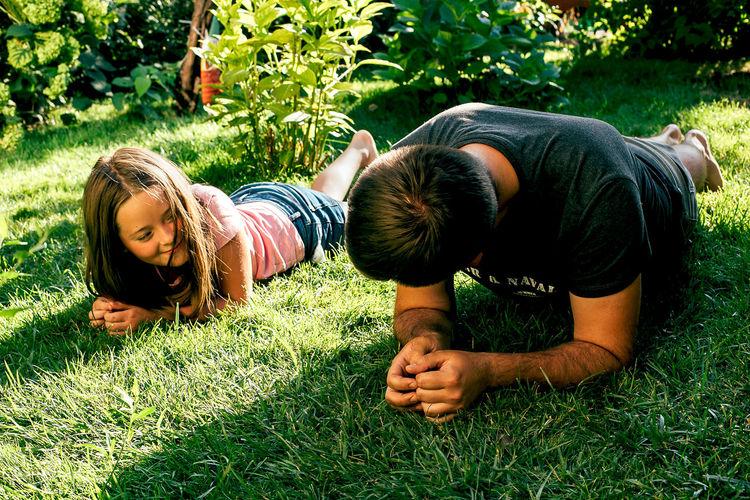 Siblings lying on field