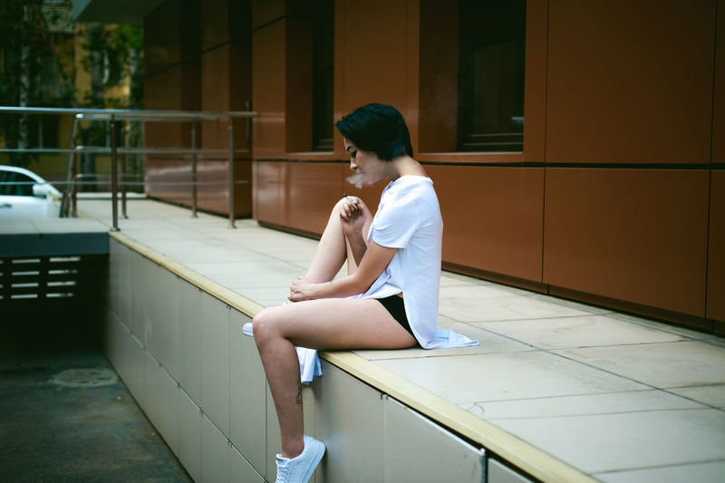Full length of young woman sitting on walkway against orange building