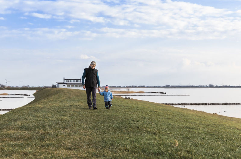 Man with toddler walking on dyke – Hindeloopen, Netherlands, Europe Ijsselmeer Adult Baby Babyhood Bonding Boy Breakwater Care Carefree Casual Caucasian Child Childhood Cloudscape Connection Distant Dyke  Exploring Family First Steps Friesland Front View Full Length Girl Grandchild Grandfather Grandparent Hiking Hindeloopen Kid Lake LeVee Love Man Mature Meadow Nature Netherlands Outdoors People Relationship Sea Shore Solitude Toddler  Togetherness Vacations Walking Wanderlust Water Grass Cloud - Sky Real People Lifestyles Two People Day Leisure Activity Casual Clothing Positive Emotion Daughter Land Sky
