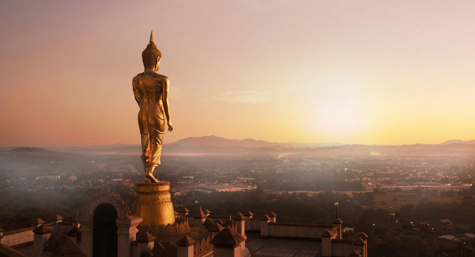 Golden Buddha Statue in the Morning,Nan province,Thailand Statue Sculpture Architecture Art And Craft Sky Sunset Built Structure City Building Exterior Creativity Tourism Nature Building Travel Male Likeness History No People Cityscape Religion Buddha