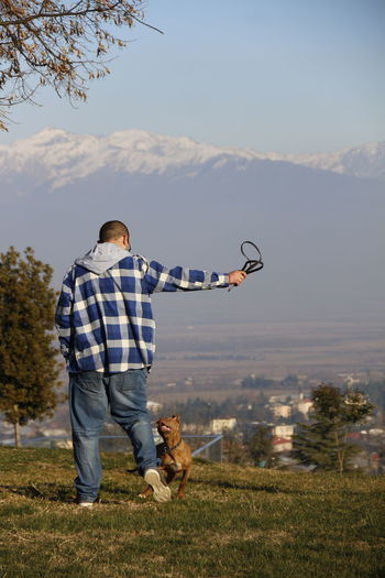 Full length of man playing with dog while standing on field at public park