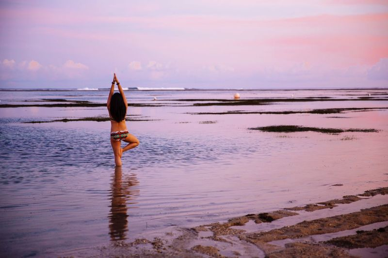 Rear view of bikini woman doing tree pose at beach against sky during sunset