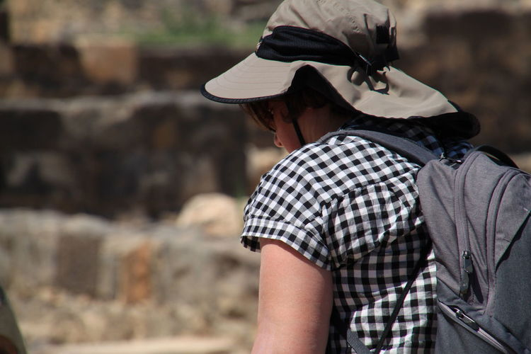 Rear view of woman wearing hat and backpack