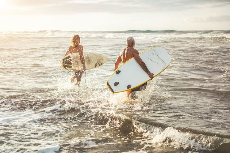 Shirtless men with surfboards walking in sea