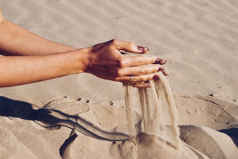 Cropped hands of woman spilling sand at beach