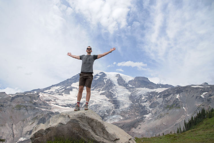 Low angle view of man standing on mount rainier against sky
