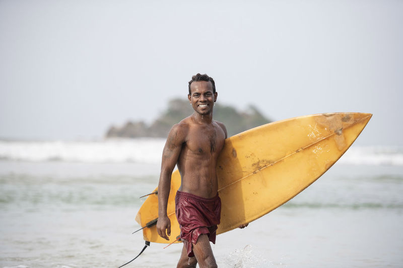 Young dark, handsome, athletic local Native Islander wearing board shorts and showing his six pack abs, walks out of the water on a tropical beach carrying his surf board Board Shorts Fun Holiday Island Life Local Native Relaxing Summertime Surfer Surfers Paradise Tropical Paradise Blue Sky Islandlife Sixpack Smiling Surf Board Tropical Island Vacation Waves, Ocean, Nature