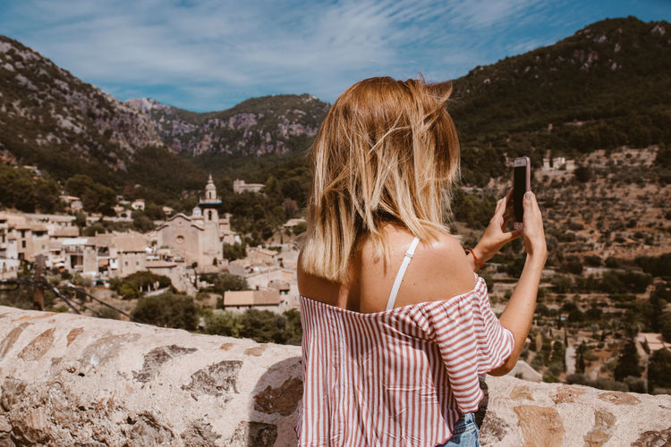 Rear view of woman using mobile phone against mountains