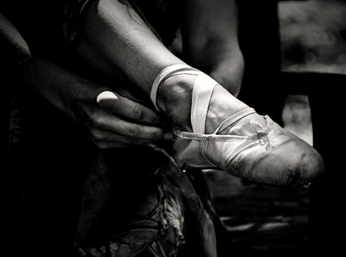 Close Up Of Ballet Dancer Tying Her Ballet Shoe
