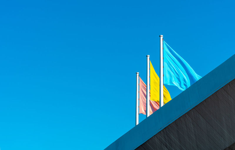 Blue Flag Sky Low Angle View Copy Space Clear Sky Patriotism No People Day Architecture Striped Yellow Built Structure Pride Multi Colored Outdoors Sunlight Environment Independence Flags In The Wind  Blue Flag Yellow Flag Red Flag 17.62°