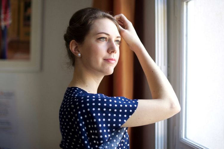 Portrait of beautiful young woman looking away at home