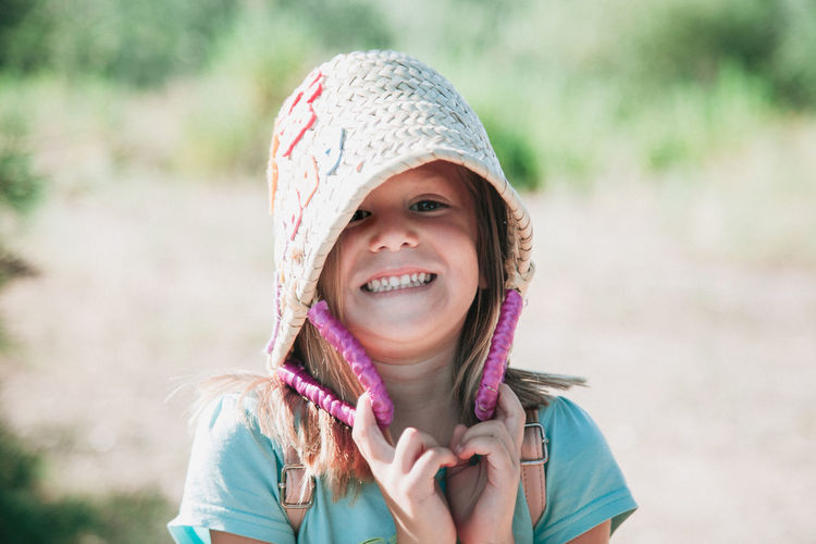 Close-Up Portrait Of Girl Smiling While Holding Basket On Field