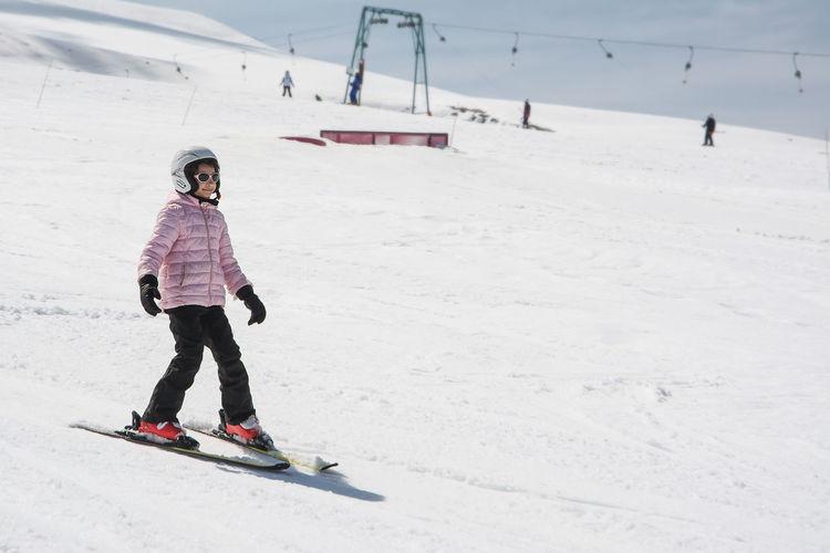 Full length of girl skiing on snow covered landscape