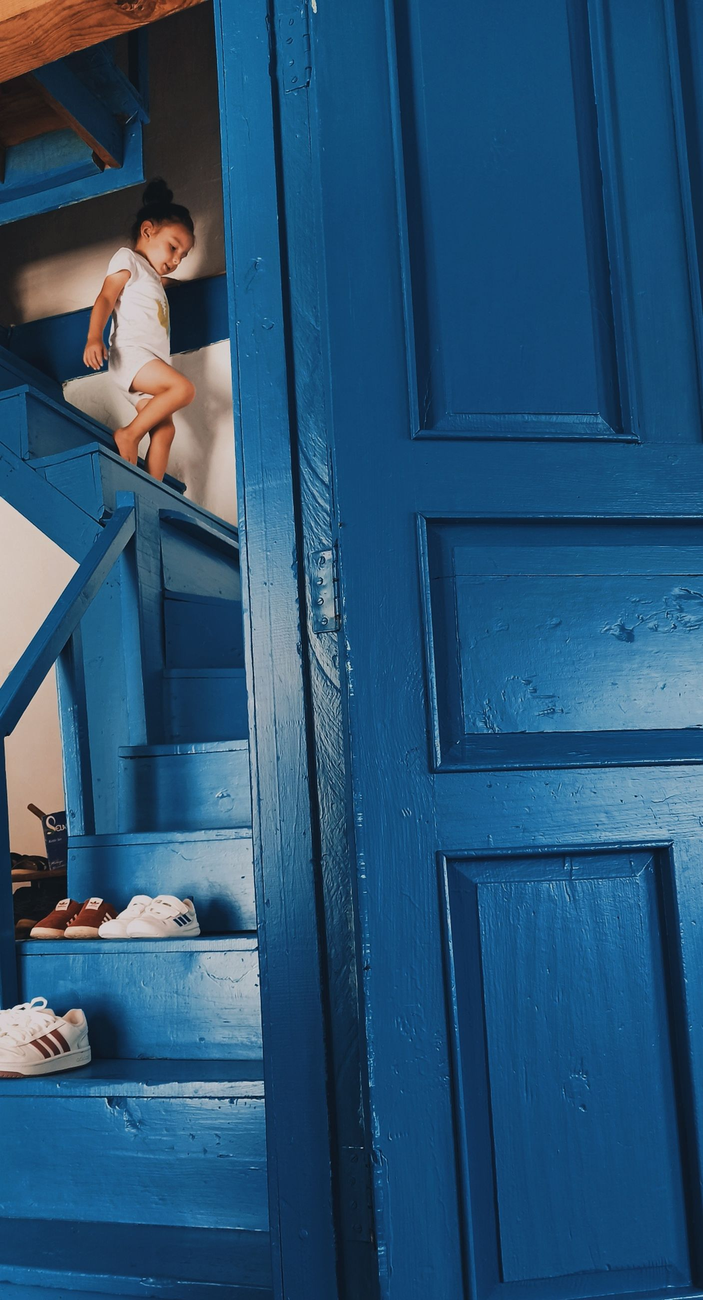 blue, door, entrance, adult, one person, architecture, young adult, wood, women, window, doorway, interior design, lifestyles, wall, room, full length, food and drink, relaxation, men, female, leisure activity, outdoors, day, built structure, standing, house, building exterior, person, emotion, looking, sitting, staircase, casual clothing
