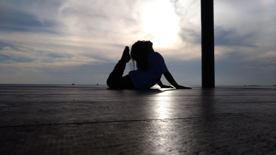 Silhouette girl practicing yoga on floorboard against cloudy sky during sunset