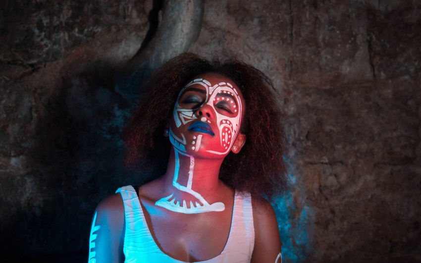 Woman with face paint and closed eyes in cave