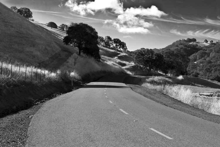 Empty Road By Hill Against Sky