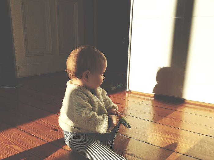 Cute girl sitting on hardwood floor at home