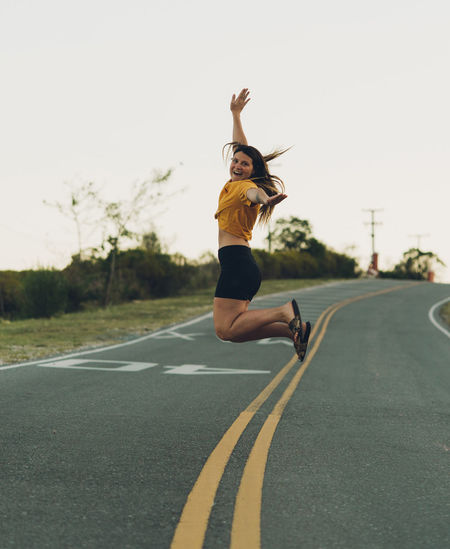 Full length of woman jumping on road against clear sky