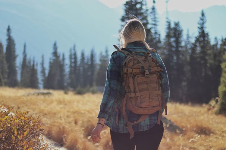 A young and married woman carries a backpack through the mountain fields during a hike